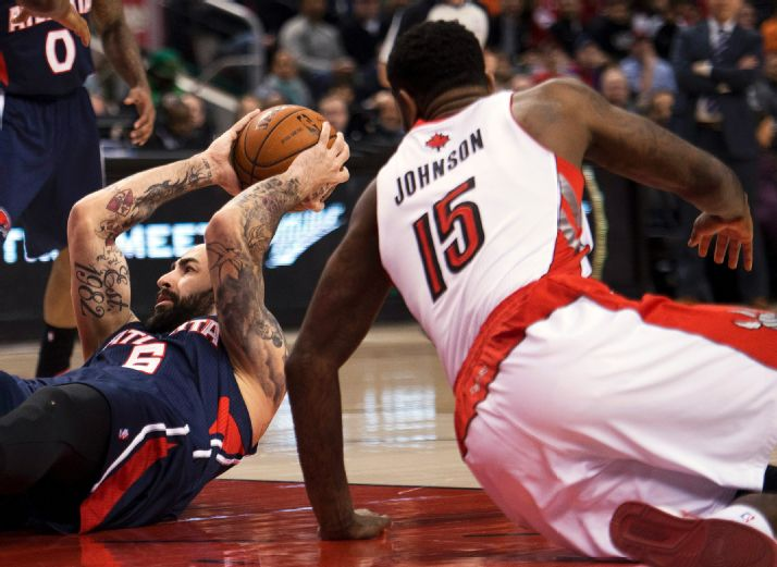 Toronto Raptors forward Amir Johnson (15) battles for the ball against Atlanta Hawks forward Pero Antic, left, during the first half of an NBA basketball game in Toronto on Sunday, March 23, 2014. (AP Photo/The Canadian Press, Nathan Denette)