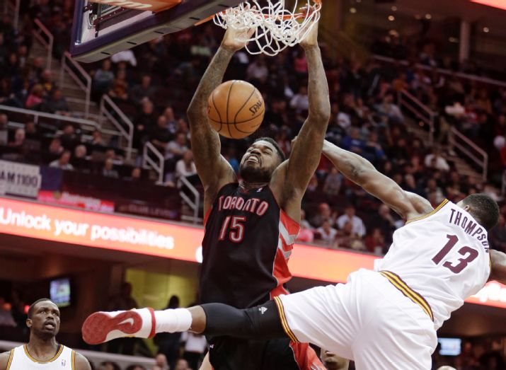 Toronto Raptors' Amir Johnson (15) dunks next to Cleveland Cavaliers' Tristan Thompson (13) during the third quarter of an NBA basketball game Tuesday, March 25, 2014, in Cleveland. Cleveland defeated Toronto 102-100. (AP Photo/Tony Dejak)